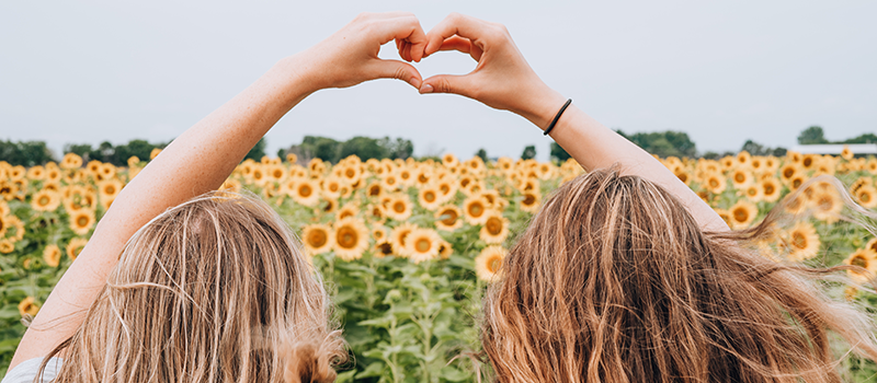 Two girls making a heart by joining their hands together in front of sunflowers
